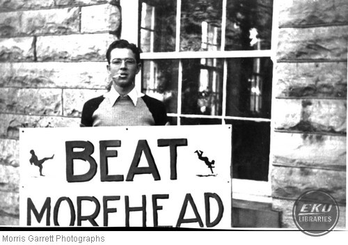"""Red"" Johnson holding a ""Beat Morehead"" sign"