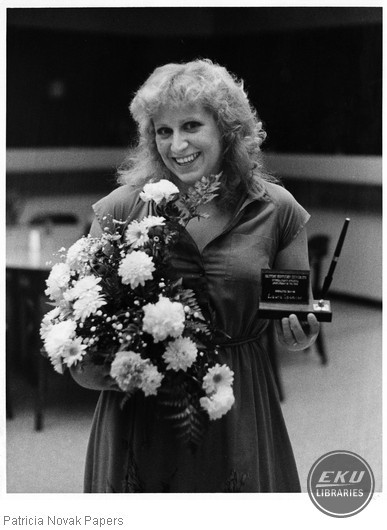 Laura Spencer holding award and flowers