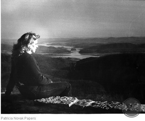Laura Spencer sitting on a ledge of a river valley