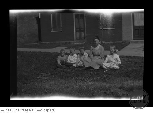 Children and an adult sitting on a lawn