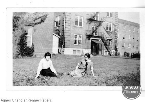 Two female students on the lawn with Sullivan Hall and a cottage behind them