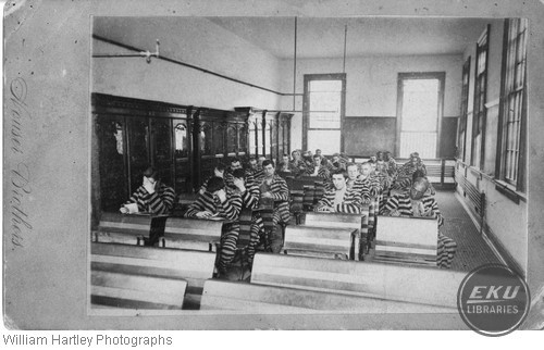 Prisoners at School Desks