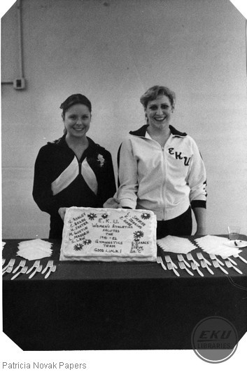 Seniors Cheryl Behne and Laura Spencer showing off the cake made for the gymnastics team