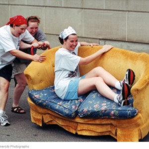 Students pushing couch with student riding